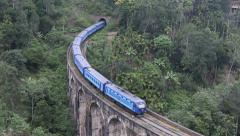 Blue train exits tunnel and crosses bridge Stock Footage