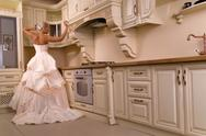 Stock Photo of beautiful bride stands in the kitchen