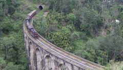Train exits tunnel and crosses bridge Stock Footage