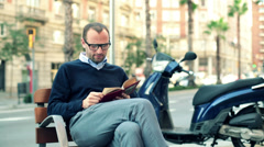Young man reading book on bench by city street HD Stock Footage
