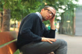 Sad, tired man sitting on bench in the city NTSC Footage