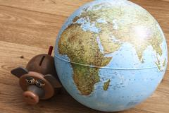 Pig money box with hand with coin and globe. pig is staring at globe. Stock Photos