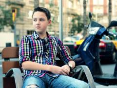 Young teenager relaxing, waiting on bench in the city NTSC - stock footage