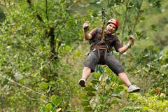Adult Man Zip Line Adventure In Ecuadorian Rainforest - stock photo