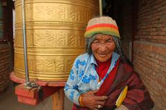 Unidentified old Tibetan spends her lifetime in a Tibetan Buddhism Temple Stock Photos