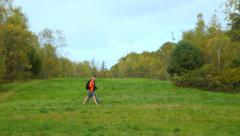 Hiking through a big open field in early autumn, medium shot. Stock Footage