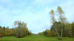 Hiking through a big open field in early autumn, wide shot. Stock Footage