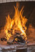 A stack on fire wood ablaze in an open fire Stock Photos