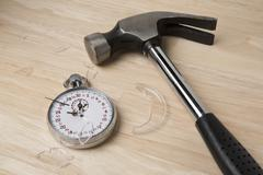 A claw hammer lying next to a broken stopwatch Stock Photos