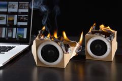 Two eco friendly cardboard audio speakers on fire next to a laptop Stock Photos