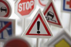 A toy hazard sign surrounded by other various road warning signs Stock Photos
