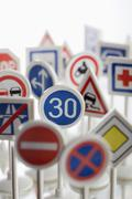 A toy speed limit sign surrounded by other various road warning signs Stock Photos
