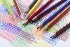 Colored pencils lying on a drawing with colored scribbles Stock Photos