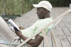 Man reading and relaxing on deck chair - stock photo