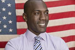 Happy businessman in front of American flag - stock photo