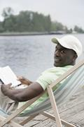 Man relaxing with book on deck chair by lake - stock photo