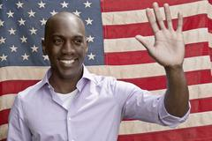 Elected politician waving in front of American flag - stock photo