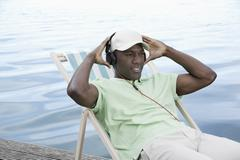 Man relaxing on deck chair by lake wearing headphones - stock photo
