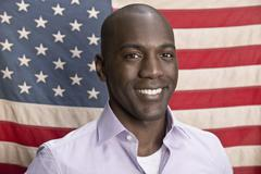 Smiling man in front of American flag - stock photo