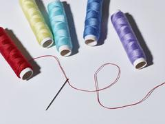 A threaded needle lying below five spools of different colored thread Stock Photos