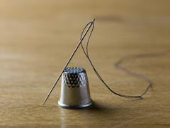 A threaded needle balanced against a shiny metal thimble Stock Photos