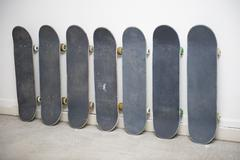 Row of skateboards against wall, one has a painting of an American Indian on it Stock Photos
