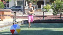 Little Girl Runs and Kicks Beach Ball and Laughs Stock Footage