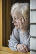 A senior woman leaning on a window sill, looking contemplative Stock Photos