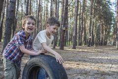 Two young boys pushing a tire in a wooded area Stock Photos