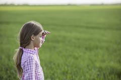 A young girl standing in a field, shielding her eyes and looking at view - stock photo