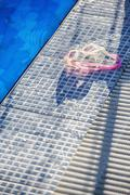 Sunlight shining on a pair of swimming goggles on the edge of a swimming pool Stock Photos