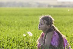 A young girl kneeling down to look curiously at a dandelion in a field Stock Photos