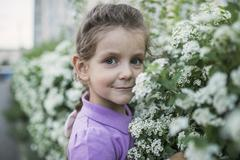 A young girl smelling flowers Stock Photos