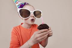 A girl wearing novelty sunglasses and party hat blowing out birthday candle Stock Photos