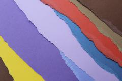 Torn pieces of various colored construction paper arranged into a pattern Stock Photos