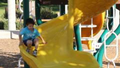 Little Boy Slides Down Yellow Slide Stock Footage