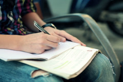 Teenager writing notes in notebook, doing homework NTSC Stock Footage