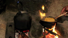 Cooking dal curry over open flame wood stove Stock Footage