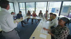 Mixed ethnicity business group in boardroom meeting or training seminar - stock footage