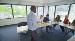 Mixed ethnicity business group in boardroom meeting or training seminar Stock Footage