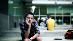 Sad, bored teenager sitting by the building HD Stock Footage