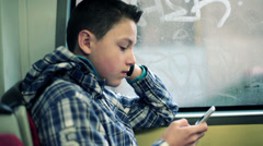 Young boy texting on smartphone while riding bus in city HD - stock footage