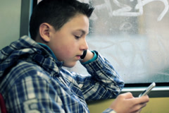 Young boy texting on smartphone while riding bus in city NTSC - stock footage