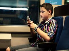 Young boy sending sms, texting on cell phone in metro train NTSC - stock footage