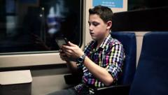 Young boy with tablet computer riding metro train HD Stock Footage