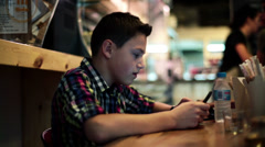 Boy with tablet computer sitting in cafe HD Stock Footage
