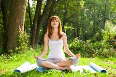Young girl doing yoga (lotus pose) in the park - stock photo