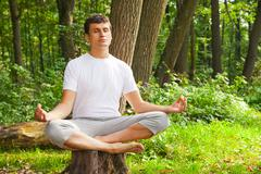 young man doing yoga (lotus pose) in the park - stock photo