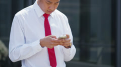 Young asian businessman checking his phone in the city  Stock Footage