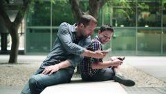 Father with son looking at something on smartphone HD Stock Footage